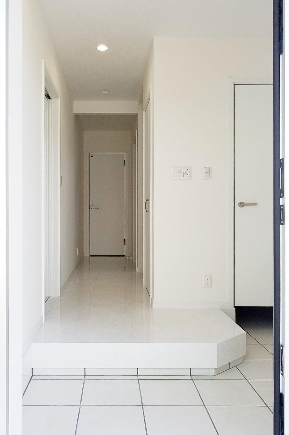 白色の鏡面床で明るく開放感のある玄関になっています。