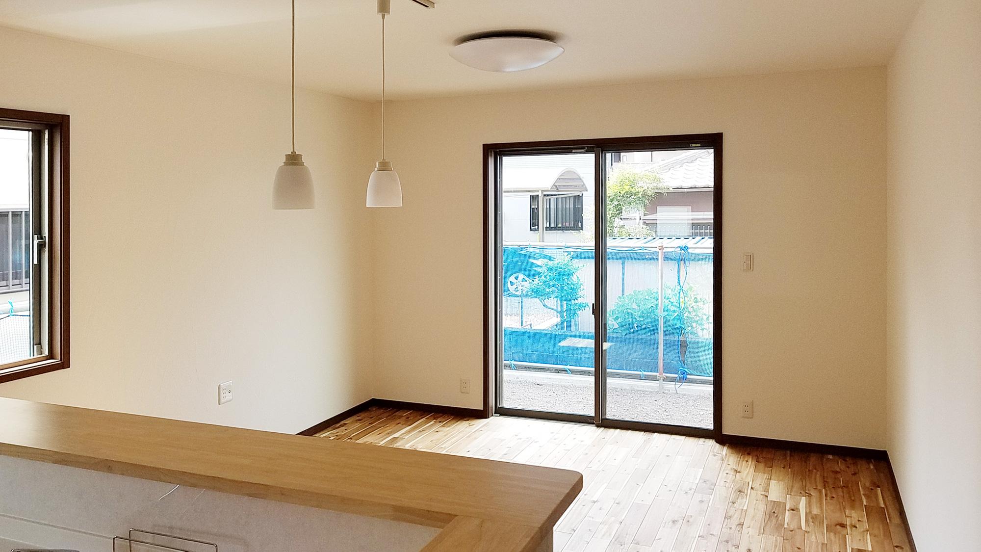 LDKはアカシアの無垢床を使い暗めに、それに合わせて建具、窓枠、巾木も濃いめの茶色を使ってシック調に仕上げましたが、暗すぎないように、アクセントにキッチンカウンターは明るめの色を選びました。