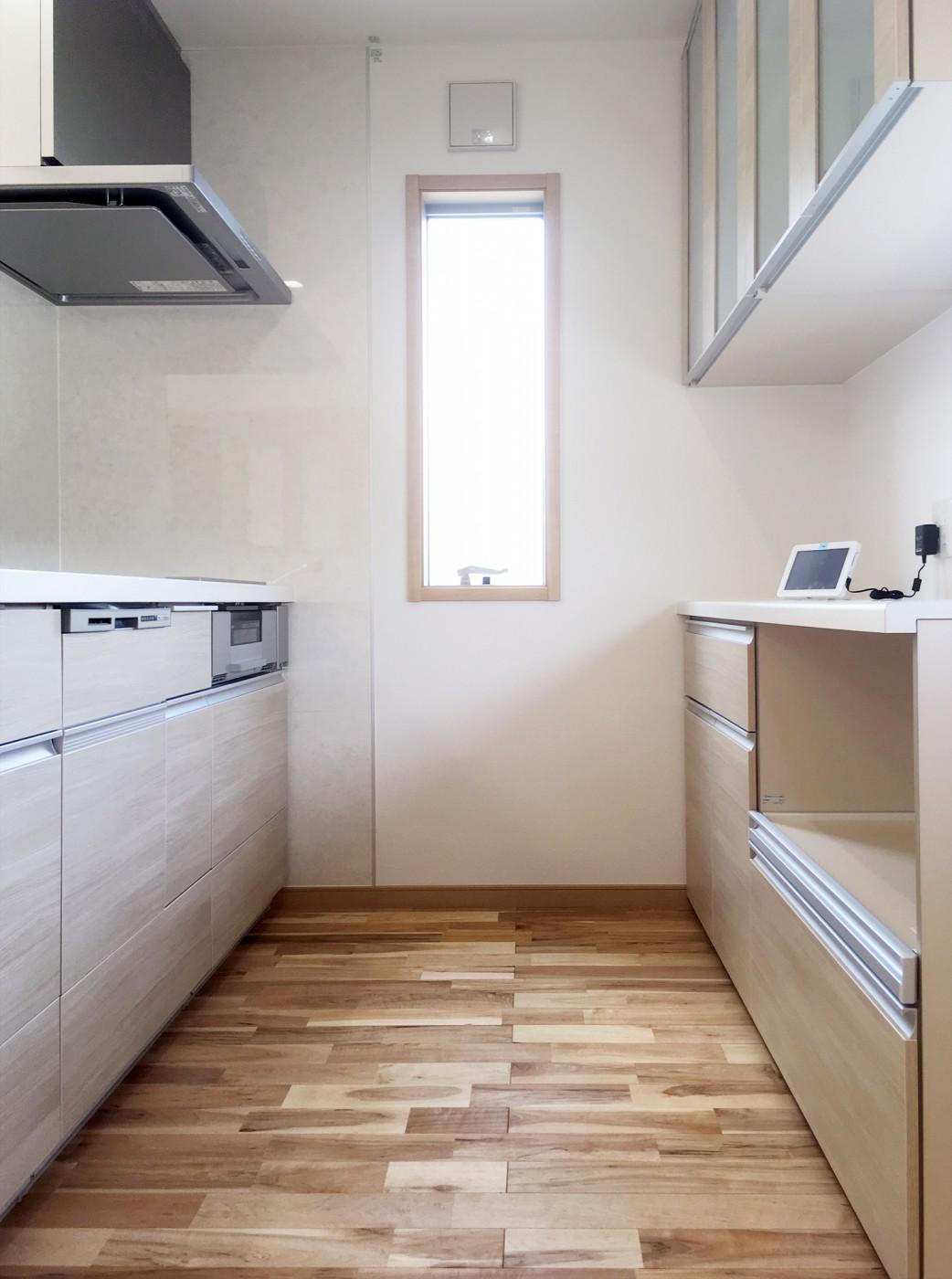システムキッチン、カップボードは無垢の床とイメージを合わせた扉カラーをチョイス。