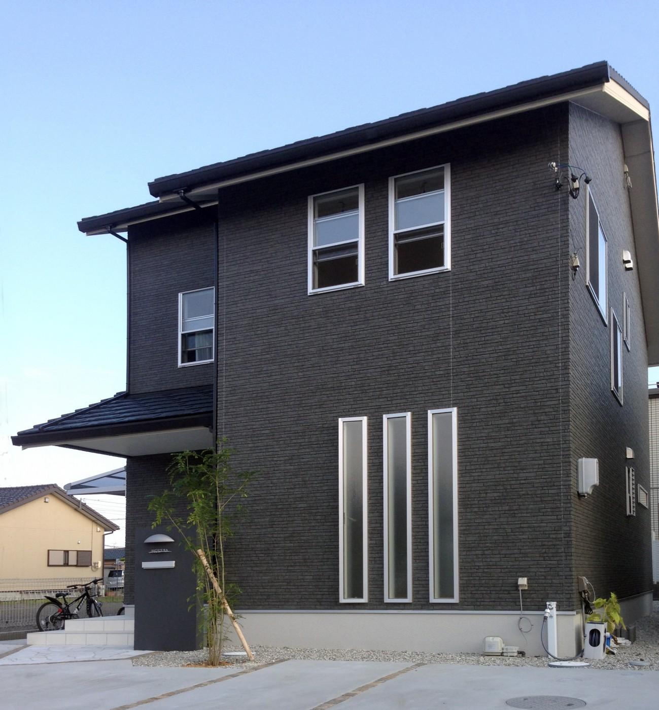 ダークな色調の外観にシンボルツリーが映えるお家です。